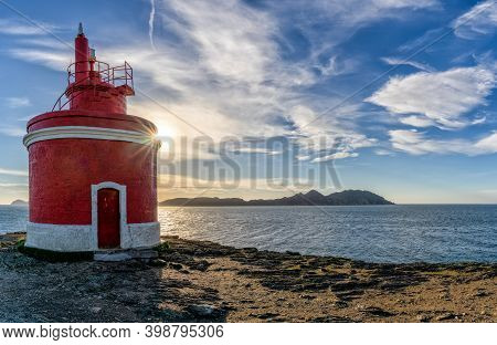 The Golden Sun Behind The Punta Robaleira Lighthouse In Galicia And The Cies Islands Behind