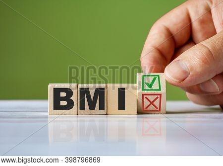 The Hand Turn Wooden Block With Red Reject X And Green Confirm Tick As Change Concept Of Bmi. Word B