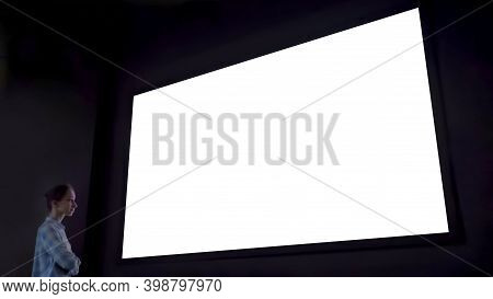 Woman Looking At Large Wall Blank Interactive White Display In Dark Room Of Modern Technology Exhibi