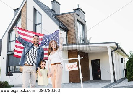 Cheerful Couple With Daughter Holding American Flag While Looking At Camera Near House And Sign With