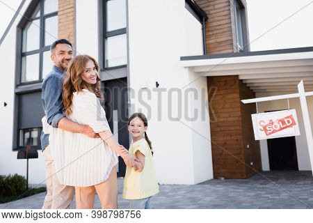 Happy Family With Daughter Hugging And Looking At Camera Near Sign With Sold Lettering And House