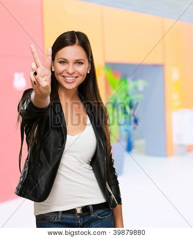 Beautiful Woman Giving Victory Sign against an abstract background