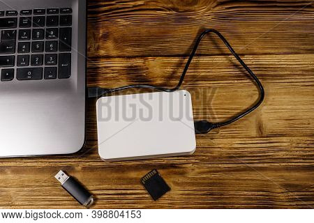 External Hdd Connected To Laptop Computer, Sd Memory Card And Usb Flash Drive On A Wooden Desk. Top