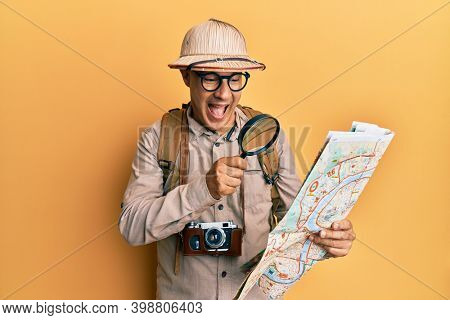 Middle age bald man wearing explorer hat holding magnifying glass on a map smiling and laughing hard out loud because funny crazy joke.