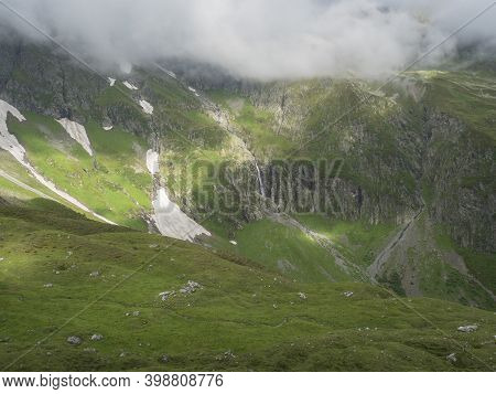 View On Green Mountain Slopes With Waterfall From Melting Snow, Summer Sunny Day With Low Fog And Cl