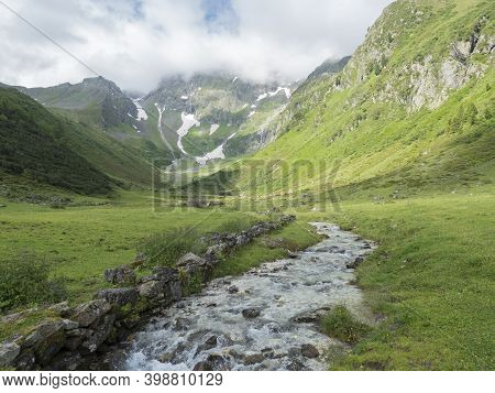 View On Stubaital Valley And Alpine Meadow With River Stream And Grazing Cows, Alpine Landscape Of T