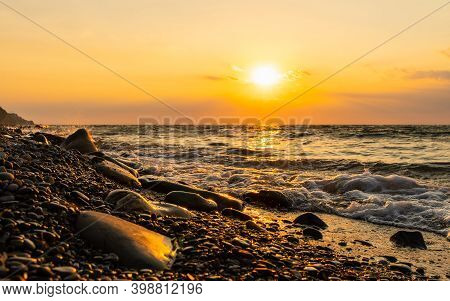 Rocky Seashore Against The Sunset. A Golden Sunset On The Seashore And A Foaming Sea. Focusing On Th