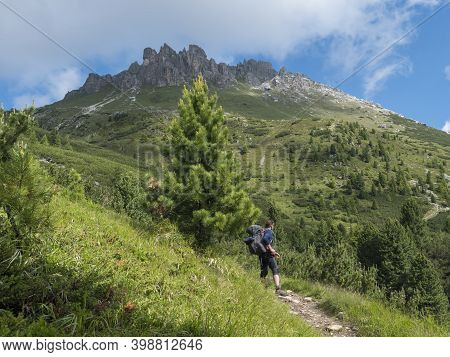 Man Hiker With View On Limestone Moutain Peaks And Pine Trees At Stubai Hohenweg, Alpine Landscape O