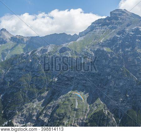 Paraglider Fly Over Limestone Mountain Peaks. Kiting In Blue And Orange Kite In Stubai Valley Tirol