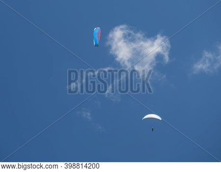 Two Paragliders Fly Over A Blue Sky. Kiting In Blue And Orange Kite In Stubai Valley Tirol Alps, Aus