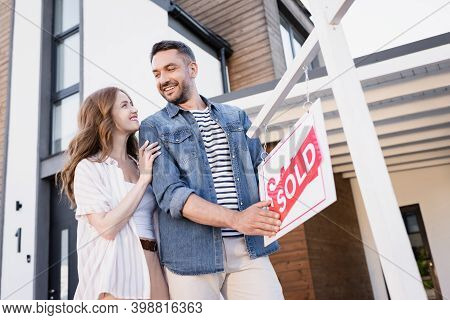 Smiling Couple Looking At Each Other Near Sign With Sold Lettering Near House