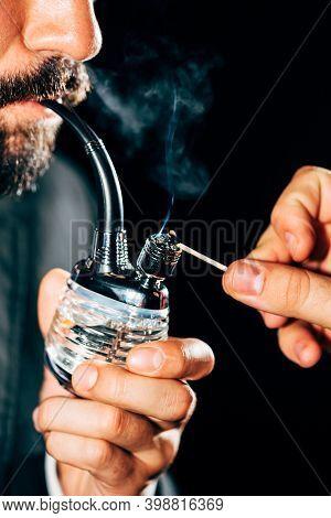 Closeup Of A Junkie's Hand Holding A Marijuana Bong And Smoking It