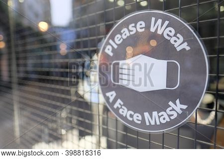 Sign On The Shop Entrance Stating Please Wear A Face Mask, Mandatory Face Covering During The Covid