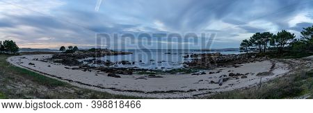 A Panorama View Of A Beach At Low Tide Under An Overcast Night Sky With Daybreak And Colorful Sunris