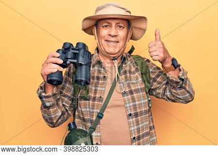 Senior man with grey hair wearing hiker bakcpack holding binoculars smiling happy and positive, thumb up doing excellent and approval sign