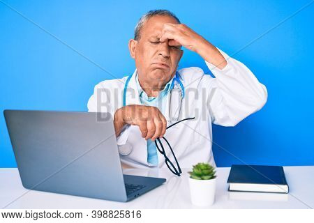 Senior handsome man with gray hair wearing doctor uniform working using computer laptop tired rubbing nose and eyes feeling fatigue and headache. stress and frustration concept.