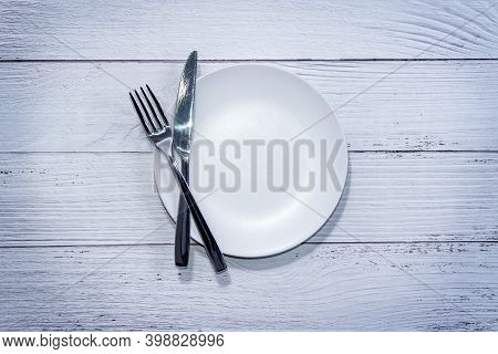 Fork And Knife On An Empty White Plate, White Wooden Table Background