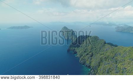 Asia mountainous isle with exotic nature variety scape. Tropical highland island aerial view at blue ocean bay. Cinematic summer scenery of Palawan islet, Philippines. Soft light drone shot