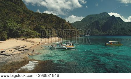 Passenger boat at ocean beach aerial view. People resting, swiming on sand at sea bay water. Amazing landscape of Philippines tropical nature with jungle forest and mountain. Cinematic paradise resort