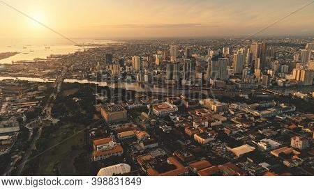 Sunrise over cityscape with green park at river shore aerial. Modern skyscrapers at business center. Traffic roadway at streets of Manila capital city, Philippines, Asia. Cinematic sun rise