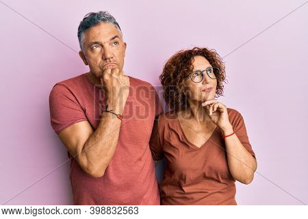 Beautiful middle age couple together wearing casual clothes with hand on chin thinking about question, pensive expression. smiling with thoughtful face. doubt concept.
