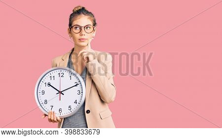 Beautiful caucasian woman with blonde hair wearing business jacket and holding clock serious face thinking about question with hand on chin, thoughtful about confusing idea