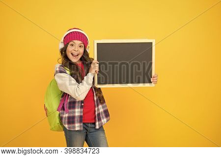 Learn Online And Have Fun. Happy Child Listen To Music Yellow Background. Little Girl Hold School Bl