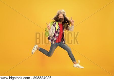 Leaping In Air. Energetic Little Child In Motion Yellow Background. Small Girl Jump High With Energe