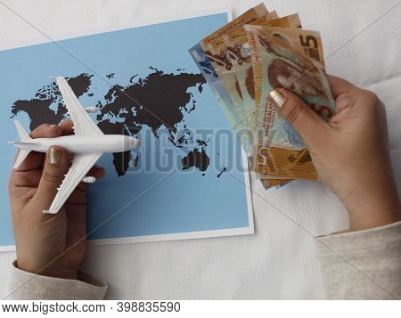 Hand Holding New Zealand Money And Figure Of An Airplane On A World Map