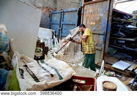 Salvador, Bahia, Brazil - December 9, 2020: Worker Is Seen Separating Material For Recycling In A Co