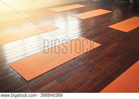 Orange Yoga Mats Lie On The Wooden Floor In The Yoga Hall.