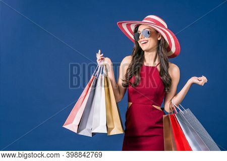 Happy Young Asian Woman Wearing Sunglasses And Carrying Multi Color Shopping Bags On Blue Color Back