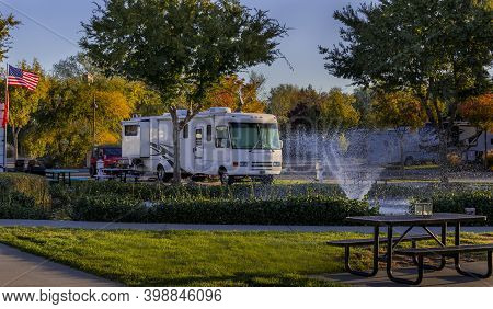 Camping In A Rv At The Rv Resort In Front Of A Water Fountain At Sunset With Lights On The Motorhome