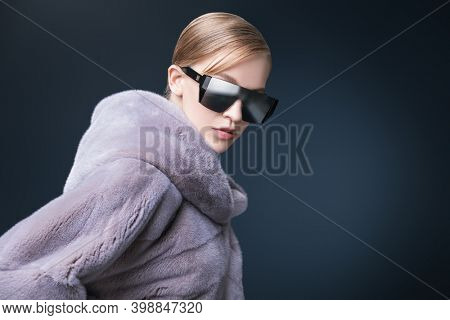 Portrait of a fashionable young woman model posing in an expensive blue mink fur coat and sunglasses on a dark blue background. Fur coat fashion.