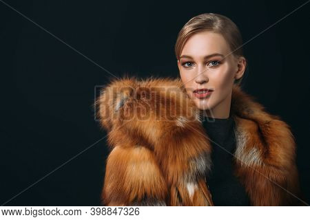 Portrait of a happy blonde girl in a fox fur coat on a black background with copy space. Winter fur coat fashion.