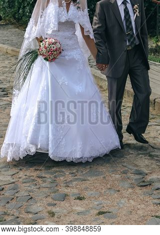 Newly Married Couple Walking On Cobblestone In The Street Of City