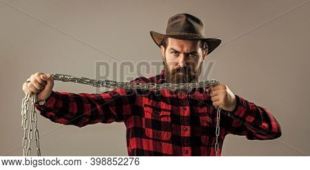 Caucasian Man With Powerful Metal Chain In Hands. Handsome Man With Beard Hold Chain. Concept Of Fre