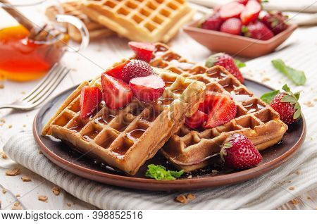 Homemade Crispy Belgian Waffles Served With Strawberries And Honey