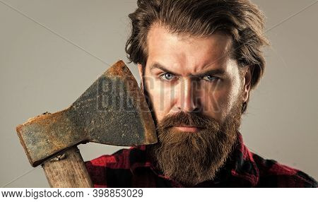 Man Holds An Ax In His Hand. Bearded Lumberjack With An Axe. Woodcutter In A Plaid Shirt. Lumberjack