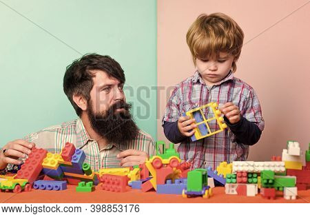 Father And Son Create Colorful Constructions With Bricks. Bearded Father And Boy Play Together. Dad