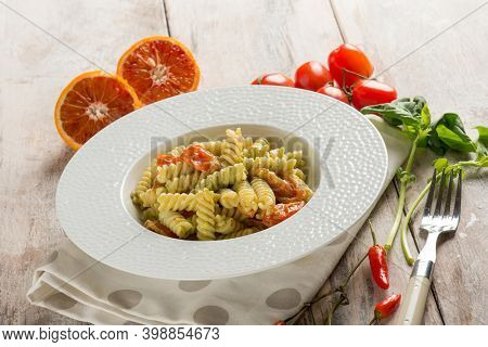 pasta fusilli with basil pesto and orange grated peel