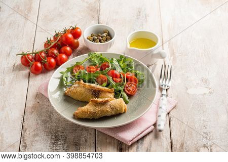 rolled sword fish with capers arugula and tomatoes salad