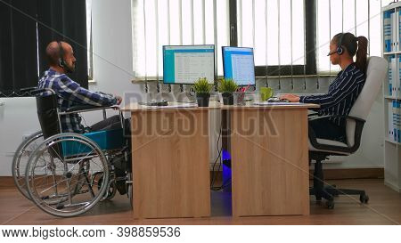 Paralysed Businessman In Wheelchair Using Headset Making Telemarketing And Offering Customer Support
