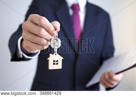 Home Sales Agents Are Giving Home Keys To New Homeowners. Landlords And House Keys Concept