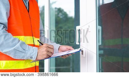 The Inspector Or Engineer Is Inspecting The Building Structure And The Glass Door Structure. After T