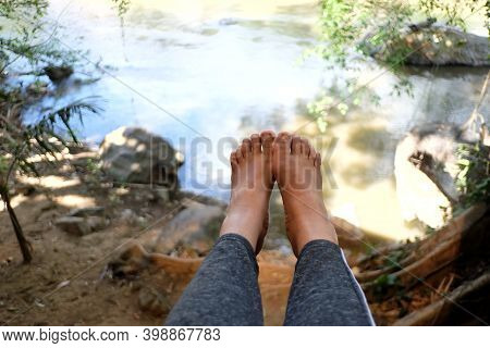 A Female Foot Hanging From A Balcony With Blurred A River View And Water Suface In A Bright Day (rel