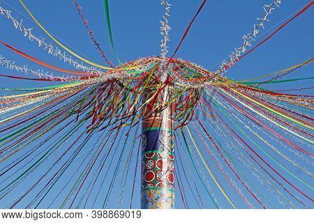 Moscow, Russia - February 25, 2020: Festive Wooden Pole With Wheel, Colourful Ribbons And Garland At