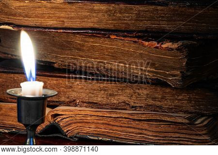 Old Worn Leather-bound Book Stack And Burning Candle In The Dark. Selective Focus. Low Key