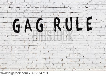 Inscription Gag Rule Written With Black Paint On White Brick Wall.