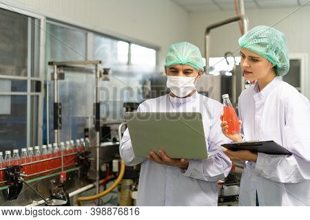 Female Quality Inspection Hold A Non-standard Juice Bottle. The Prince Records The Mistake Of An Amb